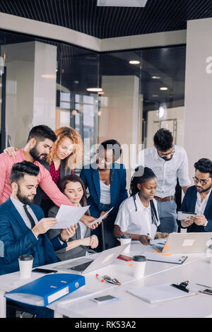 Die Suche nach neuen Erkenntnissen und geniale Ideen. Mixed-Race Gruppe von neun unterschiedlichen Menschen surfen im Netz und suchen durch Dokumente während der Sitzung am - Stockfoto