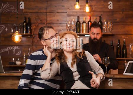 Junge Paare an der Theke sitzen und Zuneigung. Spaß haben im Pub. - Stockfoto