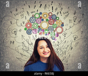 Nahaufnahme, Porträt einer jungen Frau mit bunten Zahnrad Gehirn über dem Kopf. Happy Emotion, positives Denken mit Pfeilen und Kurven Durcheinander als Gedanken. - Stockfoto