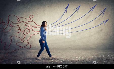 Konzept der Informationsverarbeitung als konzentrierte Frau zu Fuß über graue Wand Hintergrund als Chaos Linien kommen durch ihren Körper und in str-Umwandlung - Stockfoto