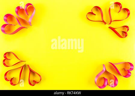 Herzen aus Rosa und Rot, Satinband auf gelbem Hintergrund mit Kopie Raum in der Mitte, die Aussicht von oben. Valentines Tag Konzept. - Stockfoto