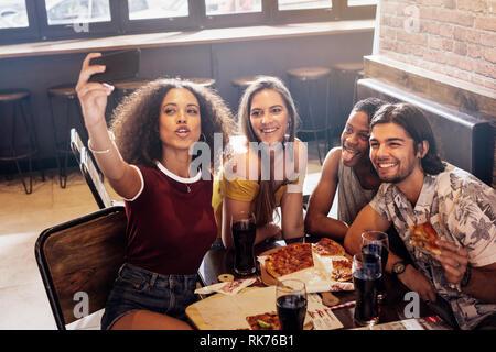 Eine Gruppe von Freunden einen selfie im Restaurant. Multi-ethnischen Mann und Frau im Cafe Erfassen einer selfie im Handy. - Stockfoto