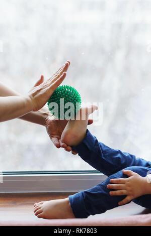 Mutter Fußmassage, Baby. Frau hält Massage Ball in der Hand. Kind sitzt auf der Fensterbank barfuß. Die Menschen sind nicht mehr wiederzuerkennen. Prävention - Stockfoto