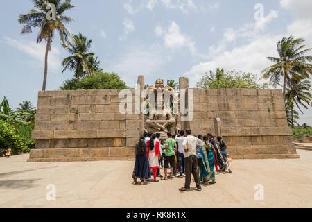 Anhänger und Besucher drängen sich die imposante Lakshmi Narasimha Tempel Statue in Hampi, Karnataka, Indien zu sehen