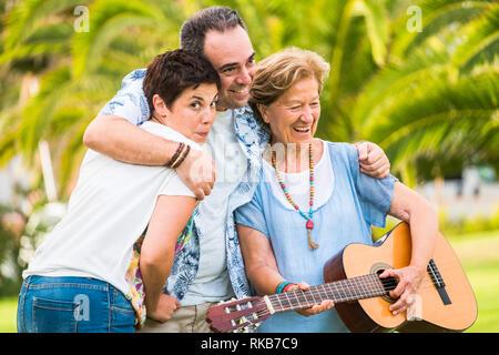 Verschiedenen gemischten Alters Generationen zusammen Spaß haben im familyh portrait Freizeit - alte Frau spielen eine Gitarre und lachen viel - grün Natur ba - Stockfoto