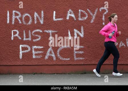 """Ein Jogger vorbei Graffiti, die lautet 'Eiserne Lady? Rust in Peace"""" Unter Bezugnahme auf frühere britische Premierministerin Margaret Thatcher in West Belfast, Nordirland, am 9. April 2013 einen Tag nach dem Tod von Thatcher. Großbritannien stand tief über das Vermächtnis der ehemaligen Premierministerin Margaret Thatcher geteilt wie die Vorbereitungen für das große Begräbnis nächste Woche der Frau rund um den Globus als die 'Eiserne Lady' bekannt. Foto/Paul McErlane - Stockfoto"""