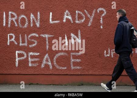 """Ein Fußgänger geht Vergangenheit Graffiti, die lautet 'Eiserne Lady? Rust in Peace"""" Unter Bezugnahme auf frühere britische Premierministerin Margaret Thatcher in West Belfast, Nordirland, am 9. April 2013 einen Tag nach dem Tod von Thatcher. Großbritannien stand tief über das Vermächtnis der ehemaligen Premierministerin Margaret Thatcher geteilt wie die Vorbereitungen für das große Begräbnis nächste Woche der Frau rund um den Globus als die 'Eiserne Lady' bekannt. Foto/Paul McErlane - Stockfoto"""