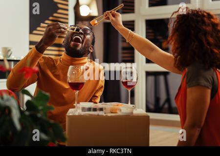 Curly Frau Sushi Roll gemeinsam mit ihrem Afrikanisch-Mann - Stockfoto