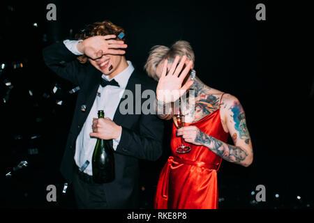 Paar für Gesicht, während sie Alkohol Getränke auf Partei isoliert auf Schwarz - Stockfoto