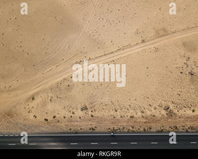 Luftaufnahme von einer Straße in die Wüste, Radfahrer Racing auf dem Fahrrad auf dem schwarzen Asphalt. Outdoor Sport, Radfahren, Tourismus. Lanzarote, Spanien - Stockfoto