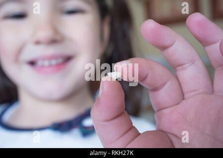 Wenig 5 Jahre altes Mädchen mit ihrem ersten Baby Zahn herausgefallen. Nahaufnahme. - Stockfoto