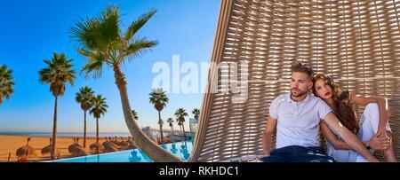 Touristische Paar in Strand Sonnenschirm am tropischen Strand im Sommerurlaub photomount. - Stockfoto