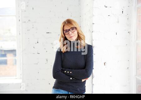 Portrait von attraktiven Frau mittleren Alters tragen Rollkragen Pullover und Jeans beim Entspannen am Fenster und Blick auf Kamera. - Stockfoto