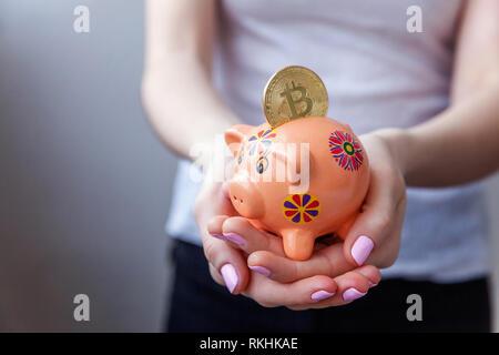 Piggy Bank, Frau Hand hält Golden bitcoin Münze virtuelles Geld. Cryptocurrency und speichern Konzept - Stockfoto