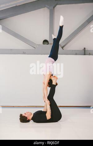 Thema ist Sport und Flächeninhalt. Eine junge Kaukasier Männlich und weiblich Paar akrobatischen Yoga üben in einem weißen Fitnessraum auf Matten. Ein Mann liegt auf dem Rücken und hol - Stockfoto