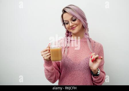 Trendige junge Frau trinkt Kaffee Milchshake. Mädchen mit jar-Becher auf weißem Hintergrund - Stockfoto