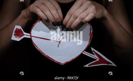 Lady hoolding dawen Herz mit roten Marken auf weißem Papier und abgeschnittenen. Sie prapered zu brach auseinander - Stockfoto