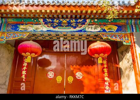 Reich verzierte rote Tür Laternen neues Jahr Sprüche Yuer Hutong Gegend Beijing China. Yuer Hutong geht zurück auf 1600. Die chinesischen Zeichen an der Tür - Stockfoto