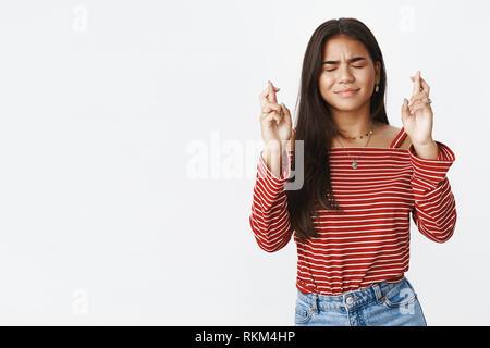 Taille - geschossen von Sorgen niedlich indischen Jugendmädchen mit dunklen langen Haaren in der Nähe Augen wie beten, wollen mit gekreuzten Fingern für gutes Glück - Stockfoto
