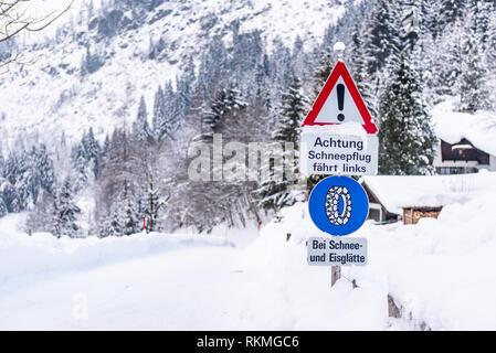Kette Verkehrsschild, bei Schnee- und Eisglätte Warnung, Winterdienst, Schneeketten Pflicht. Schnee weg und Bäume. Österreich, Europa - Stockfoto