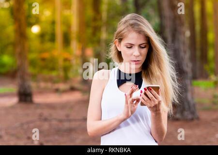 Schöne blonde junge Frau im Park bei Sonnenuntergang Abrufen von Nachrichten auf Ihr Handy - Bild - Stockfoto