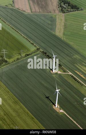 Luftaufnahme eines Windparks und Windkraftanlagen in der Mitte von Ackerland mit grünen Feldern und elektrischen Leitungen auf Pole, Niedersachsen, - Stockfoto