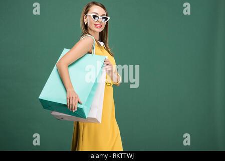 Stilvolle Frau im gelben Kleid und Sonnenbrille mit Einkaufstaschen isoliert auf Grün - Stockfoto