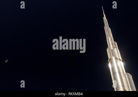 Ein Verkehrsflugzeug fliegt hoch über der hohen Kilometer hoch glänzenden Metall Struktur des Burj Khalifa, wie dem Burj Dubai in Downtown Dubai bekannt - Stockfoto