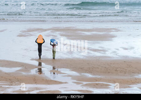 Zwei Surfer ihre surfbretter auf dem Kopf und gehen hinunter zum Meer auf den Fistral Beach in Newquay in Cornwall. - Stockfoto