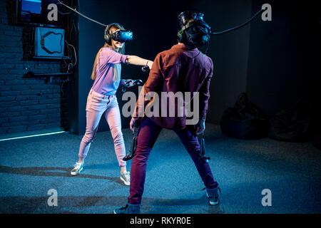 Mann und Frau spielen Spiel mit Virtual reality Headsets und Gamepads im dunklen Raum der spielenden Club - Stockfoto