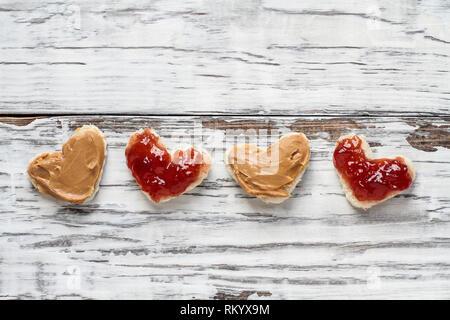 Ansicht von oben offenem Gesicht hausgemachte Peanut Butter und Marmelade herzförmige Sandwiches über einem weißen weiße Holztisch/Hintergrund. Ansicht von oben. - Stockfoto