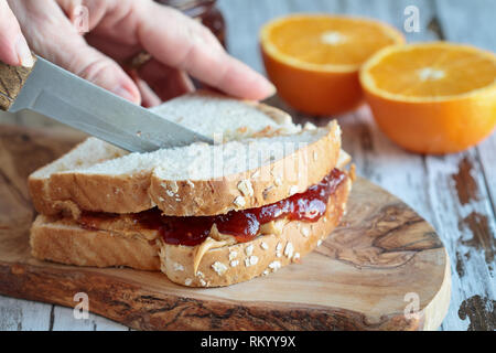 Womans Hand schneiden ein Sandwich mit Erdnussbutter und Marmelade auf einem rustikalen hölzernen Schneidebrett. Selektiver Fokus auf Sandwich. - Stockfoto