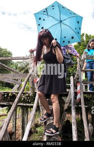 Frauen sorgfältig zu Fuß über eine Bambus Brücke im Dschungel von Sarawak Cultural Village, Damai, Sarawak, Malaysia. - Stockfoto