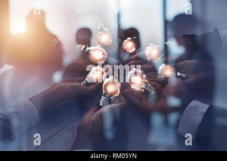 Teamarbeit und Brainstorming Konzept mit Geschäftsleuten, die eine Idee mit einer Lampe. Konzept der Start. Doppelte Belichtung - Stockfoto