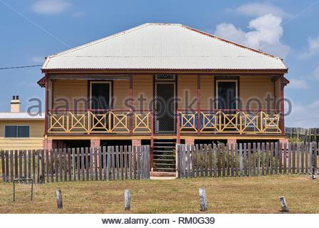 Die historische Zinn - überdacht von Schnittholz Boatman Cottages; Pilot Hügel hinter einem hölzernen erblassen - Zaun, hoch auf einem grasbewachsenen Strand entfernt; bei Yamba, Australien. - Stockfoto