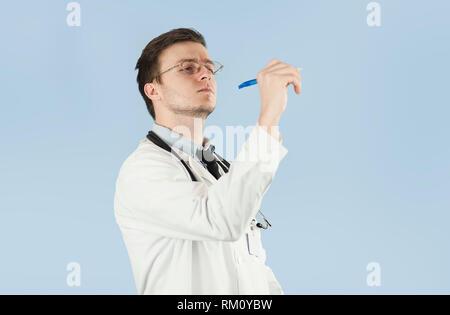 Junge männliche Arzt, medizinische Mitarbeiter, zeigt auf leeren Raum auf auf blauem Hintergrund isoliert. Konzept hält etwas in leere Hand - Stockfoto