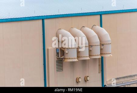 Vier Auspuffrohre auf der Seite der industriellen Gebäude - Stockfoto