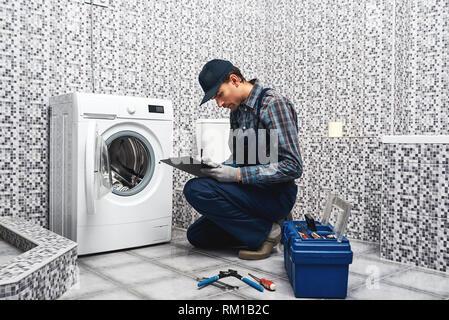Preis der Klempner arbeiten. Working Man Klempner schreiben Preis liste in der Nähe einer Waschmaschine in Wäscheservice - Stockfoto