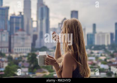 Junge Frau essen Chia Pudding auf Ihrem Balkon mit Blick auf die große Stadt - Stockfoto