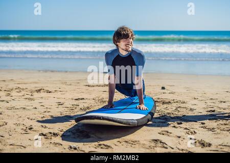 Junger Mann surfer Ausbildung vor gehen zur Aufstellung an einem Sandstrand. Lernen zu surfen. Ferienhäuser Konzept. Sommerferien. Tourismus, Sport - Stockfoto