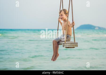 Happy Boy sitzen auf Swing am Meer bei Sonnenuntergang - Stockfoto