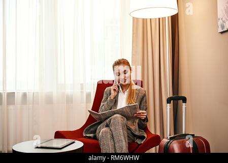 Business Call im Hotel Zimmer in der Geschäftsreise. Junge und stilvolle Geschäftsfrau mit Koffer und Smartphone sitzt auf einem Sofa im Hotel Zimmer. Digitale tablet am Tisch - Stockfoto