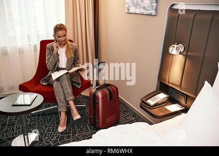 Frau, die Geschäftsreise. Junge und stilvolle Geschäftsfrau mit Koffer und Smartphone sitzt auf einem Sofa im Hotel Zimmer. Digitale tablet am Tisch - Stockfoto