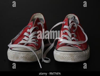 In der Nähe von Paar Turnschuhe - Rot und Weiß vintage abgenutzte Schuhe - Jugend hipster Schuhe auf schwarzem Hintergrund - Stockfoto
