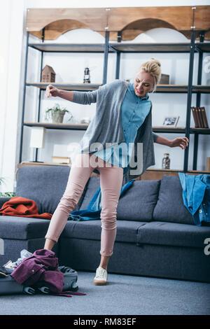 Wütende Frau drücken Kleidung im Koffer mit Bein nach oben brechen mit Freund