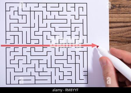 In der Nähe der Person Hand Lösung Labyrinth Puzzle mit roten Marker über Holz- Schreibtisch - Stockfoto