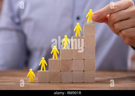 Close-up Gelb menschliche Figuren Führenden auf Holzklötze im Büro - Stockfoto