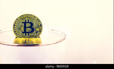 Golden Bitcoin im Fokus auf ein kässeli auf weißem Hintergrund mit Kopie Raum isoliert - Stockfoto