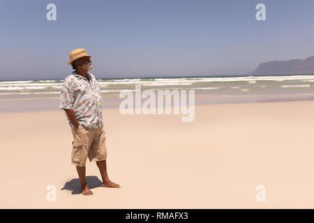 Älteren schwarzen Mann mit Hut und die Hände in der Tasche weg schauen am Strand - Stockfoto