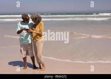 Senior paar Überprüfung Fotos auf Handy am Strand - Stockfoto
